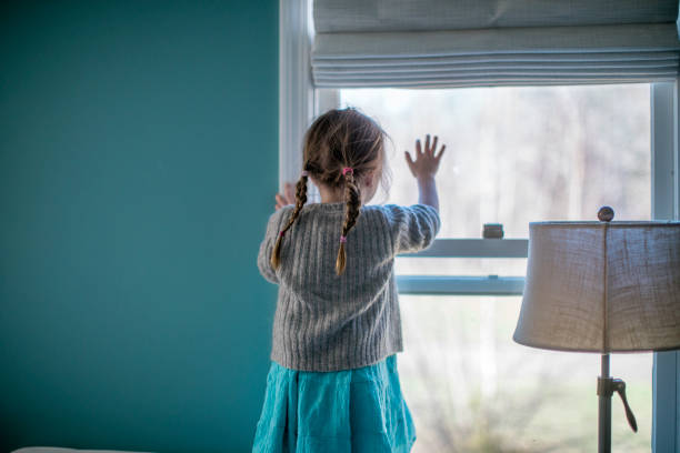Portrait of a little girl looking out of the window