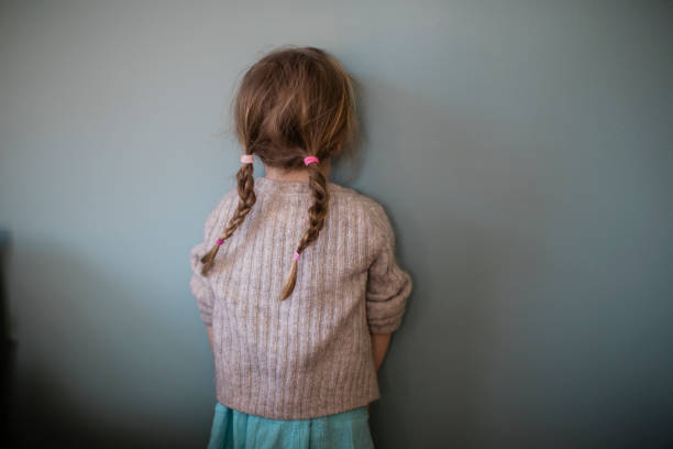 Portrait of a little girl making faces against a blue wall