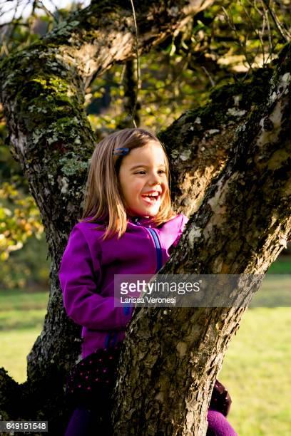 Portrait of a little girl sitting in a tree