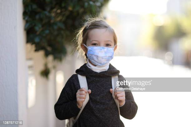 portrait of a little girl wearing a protective face mask, ready to go to school - education stock pictures, royalty-free photos & images