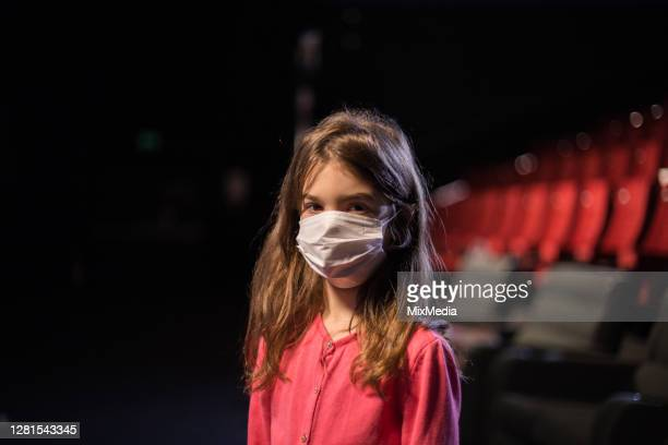 portrait of a little girl wearing a protective mask  at the cinema - film premiere stock pictures, royalty-free photos & images
