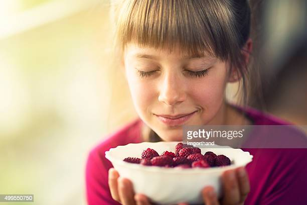 Portrait of a little girl with raspberries.