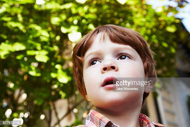 Portrait of a little red haired boy (2-3) lost in thoughts and looking content, from below