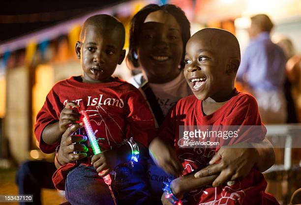Portrait of a local bahamian young mother with her two little sons children kids family at the annual Rake 'n' Scrape Festival on June 15 2012 in Cat...