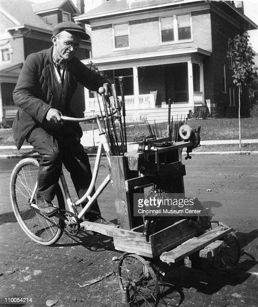 Portrait of a locksmith on a modified bicycle while tools to both make keys and repair umbrellas Cincinnati Ohio 1917
