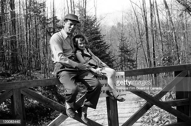 Portrait of a log driver and his daughter sitting on a fence Quebec Canada 1956 Photo taken during the National Film Board of Canada's production of...