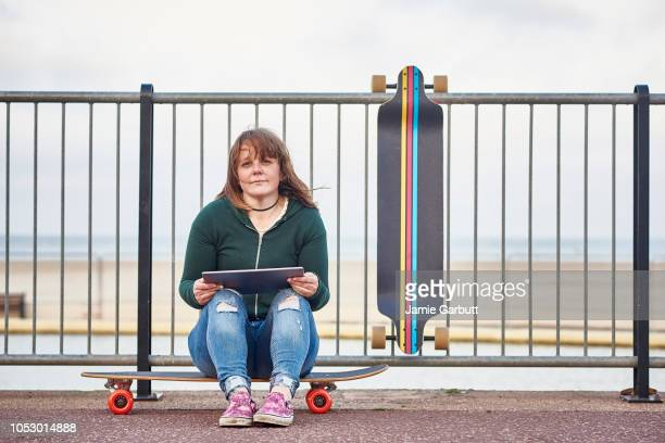 A portrait of a lone British female long boarder sat on her board with a tablet
