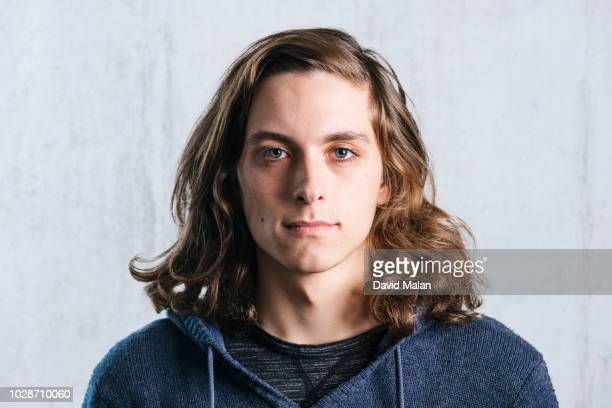 portrait of a long haired young man in a hoodie. - wavy hair stock pictures, royalty-free photos & images