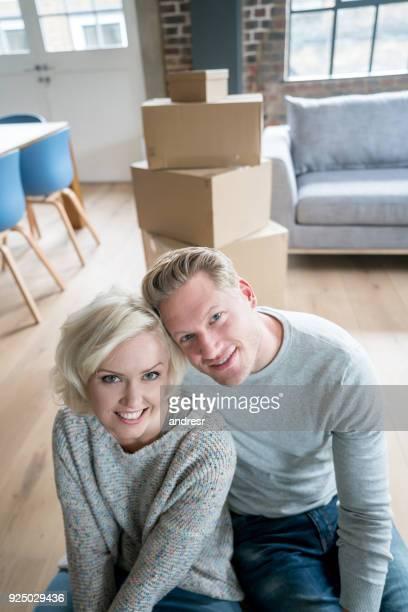 Portrait d'un couple charmant, emménager dans leur nouvelle maison regardant sourire caméra