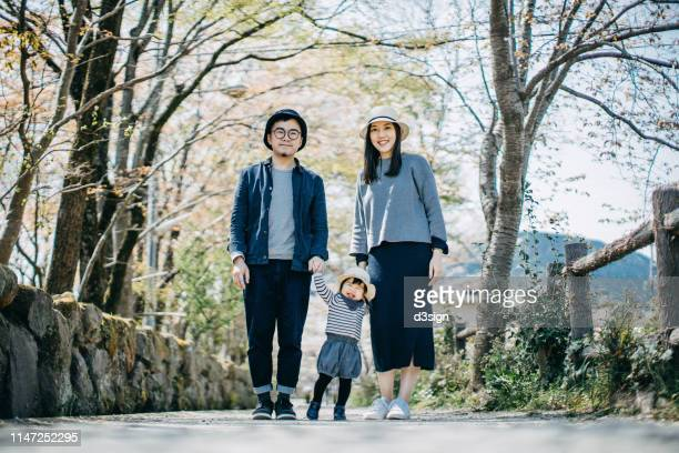 portrait of a loving family of three holding hands and enjoying intimate family time together on a lovely sunny day in the nature - 写真撮影 ストックフォトと画像