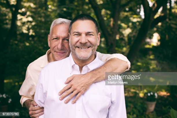 portrait of a loving middle-aged gay couple - coppia omosessuale foto e immagini stock