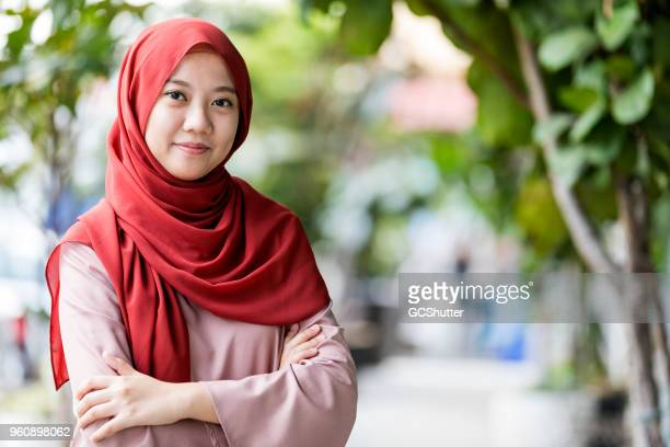 portrait of a malaysian girl at a park - malay hijab stock photos and pictures