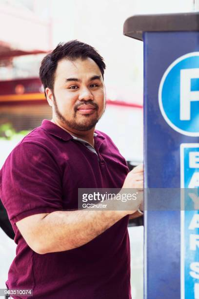 Portrait of a Malaysian man using a parking ticket machine