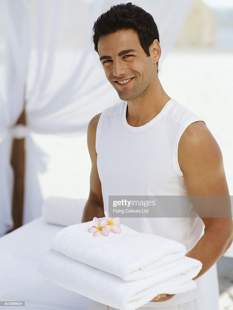 Portrait of a Male Attendant Carrying Folded Towels : Stock Photo