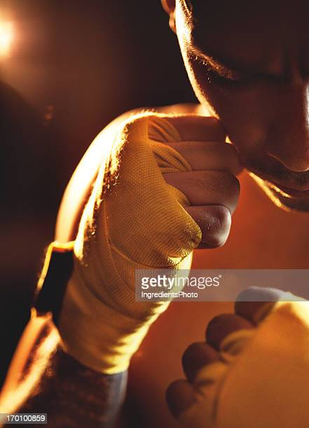 Portrait of a male boxer with yellow hand wraps.