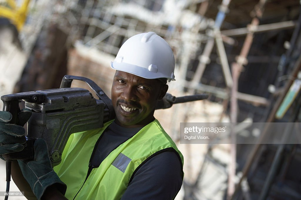 Portrait of a Male Builder in a Hard Hat, Carrying a Drill on His Shoulder : Stock Photo