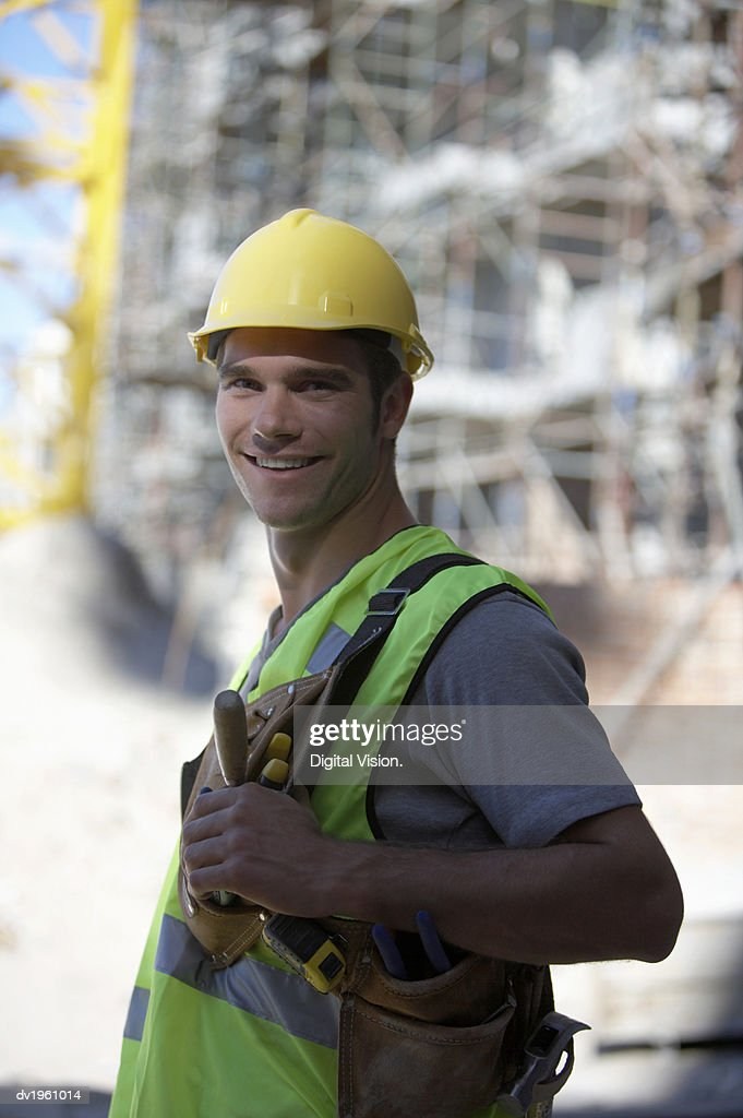 Portrait of a Male Builder Wearing a Hard Hat, Fluorescent Jacket and Tool Belt : Stock Photo