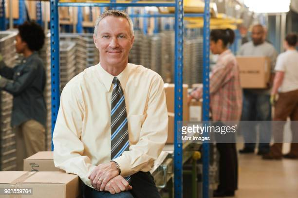 Portrait of a male Caucasian executive in a dress shirt and tie next to a motorized conveyor system in a large distribution warehouse.