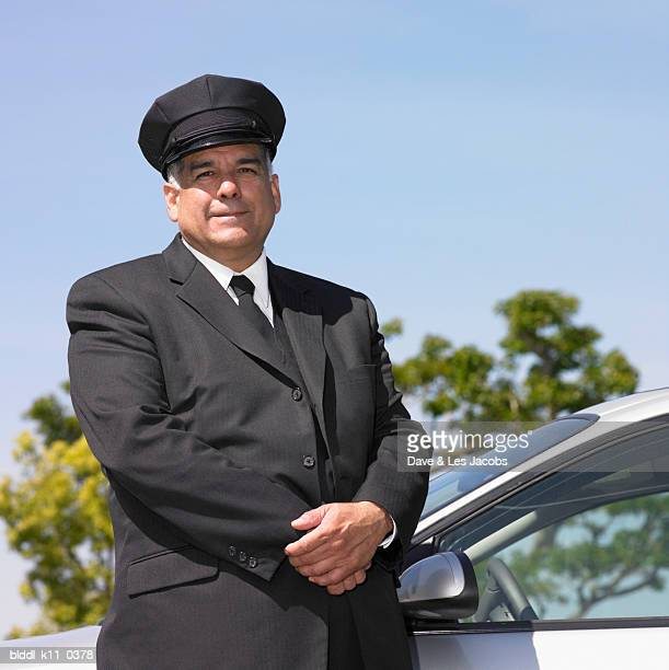 Portrait of a male chauffeur standing against a limousine with his hands clasped