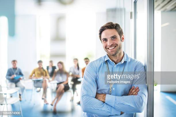A portrait of a male coach standing in a board room. A group of businesspeople sitting, making notes.