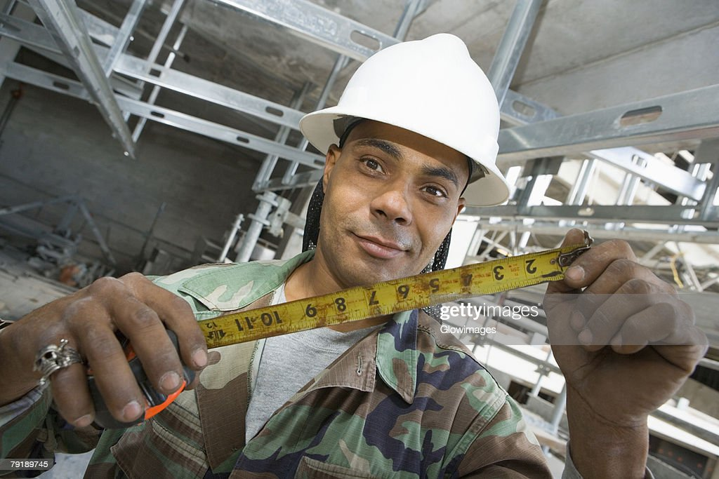 Portrait of a male construction worker holding a tape measure : Stock Photo