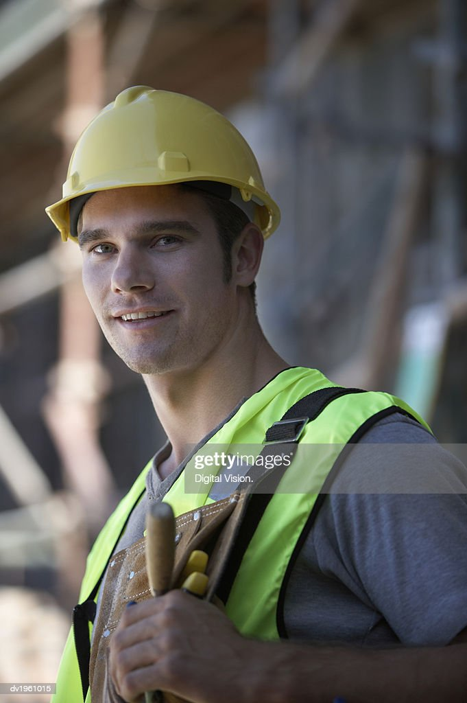 Portrait of a Male Construction Worker in a Hard Hat and Fluorescent Jacket : Stock Photo