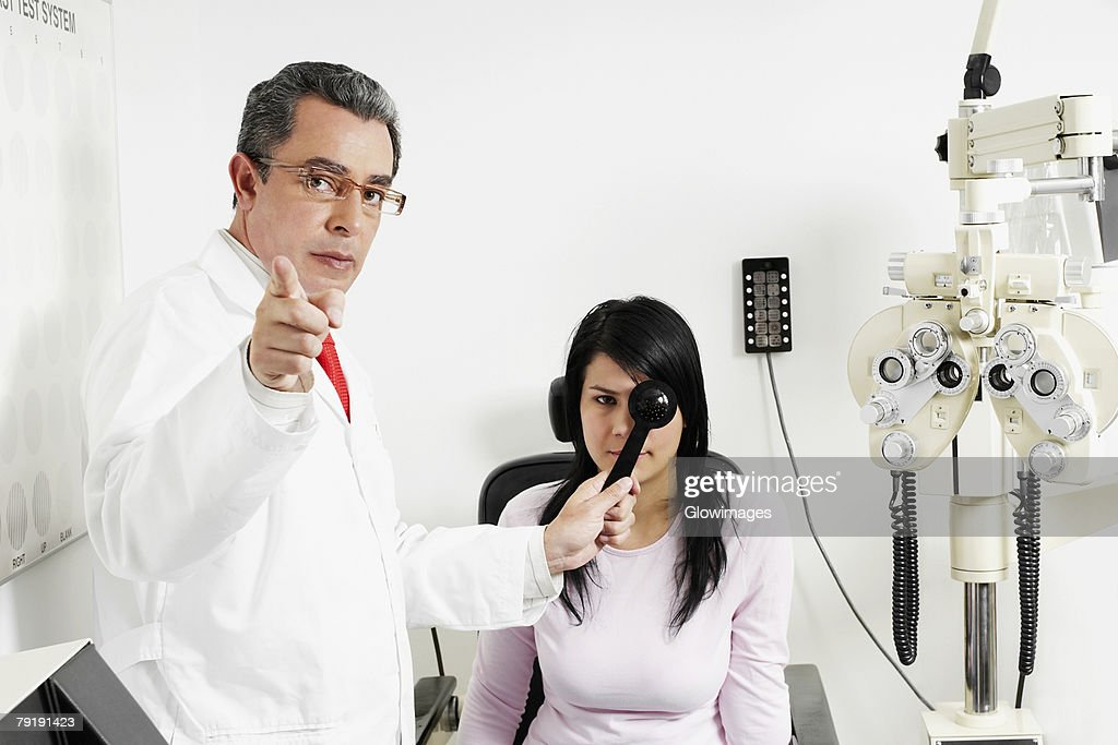 Portrait of a male doctor examining a young woman's eye : Foto de stock