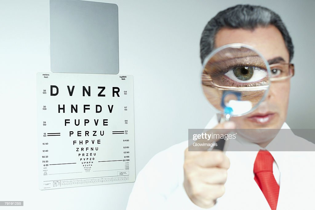 Portrait of a male doctor holding a magnifying glass in front of his eye : Foto de stock