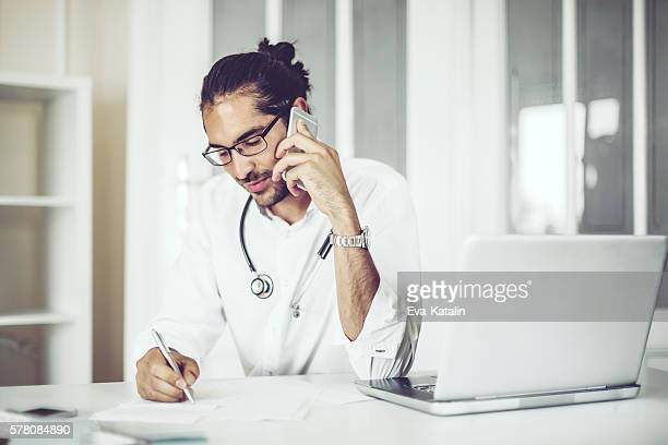 portrait of a male doctor - answering stock pictures, royalty-free photos & images