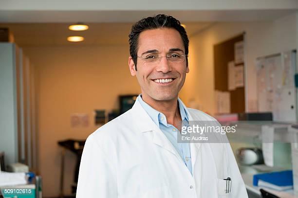 portrait of a male doctor smiling in hospital - blouse de laborantin photos et images de collection