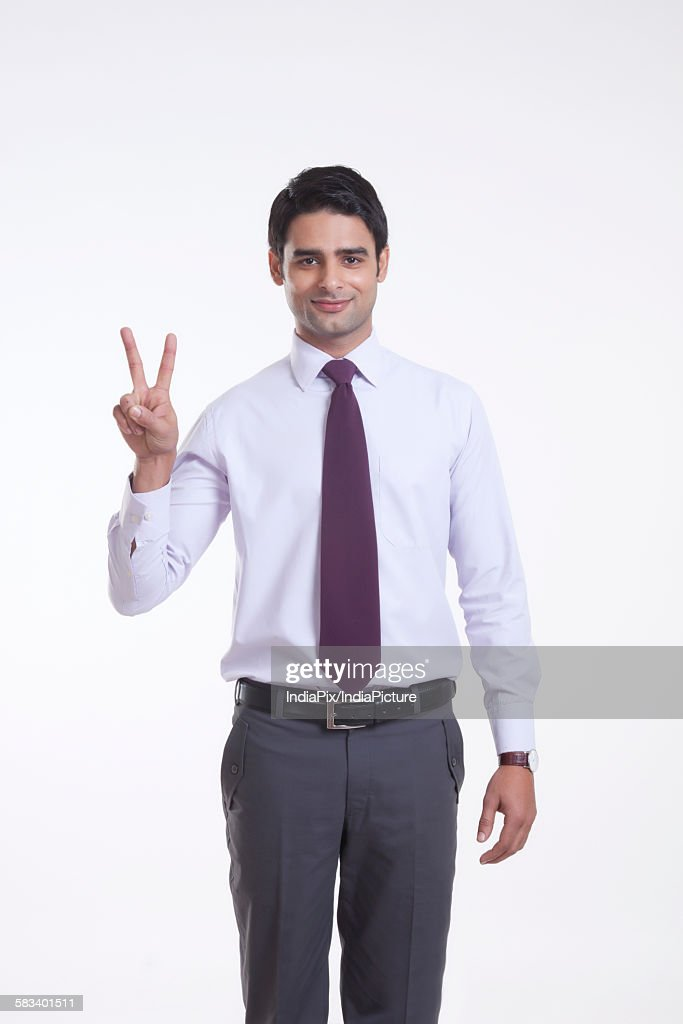 Portrait of a male executive giving peace sign : Stock Photo