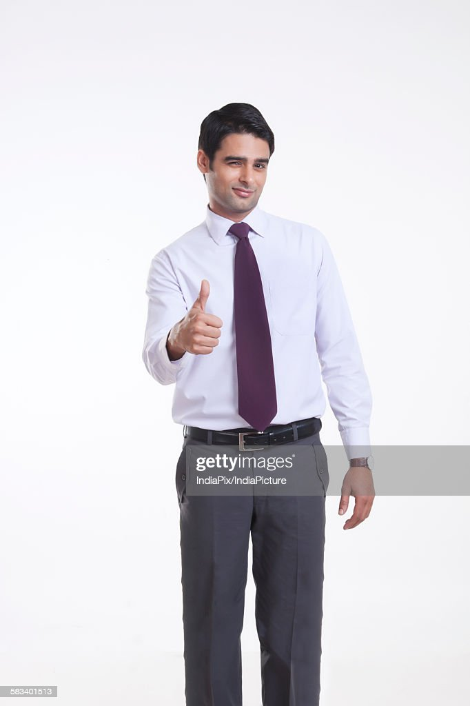 Portrait of a male executive giving thumbs up : Stock Photo