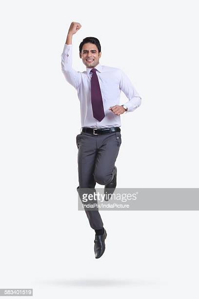 Portrait of a male executive jumping in the air