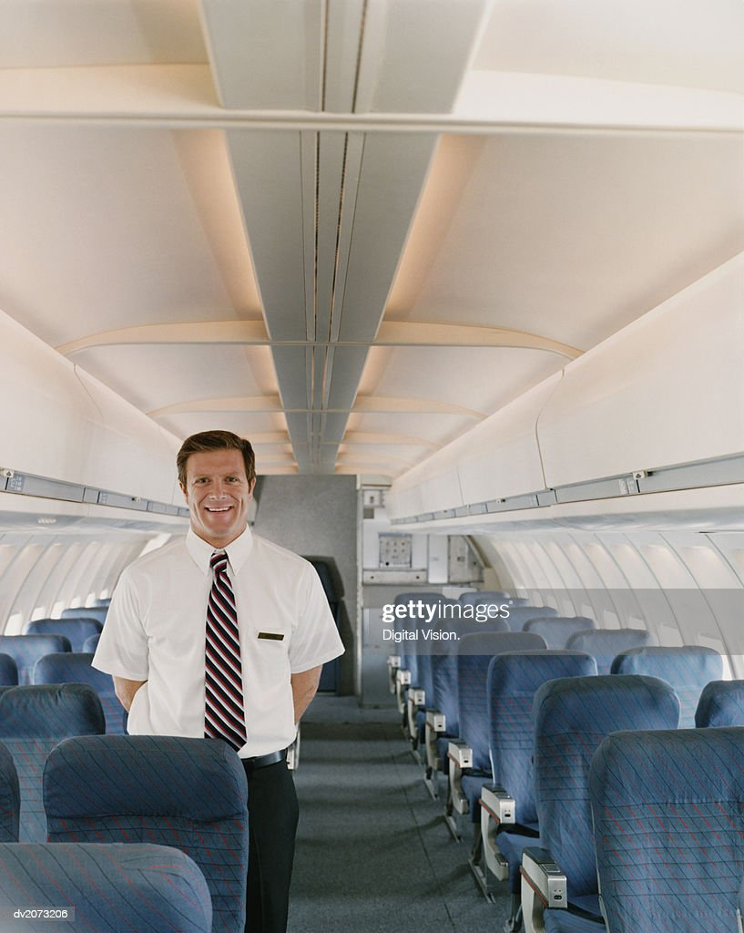 Portrait of a Male Flight Attendant on a Plane : Stock Photo