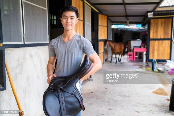 Portrait of a male horse rider holding a horses saddle