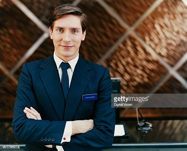 portrait of a male hotel manager standing by a reception desk - nameplate stock pictures, royalty-free photos & images