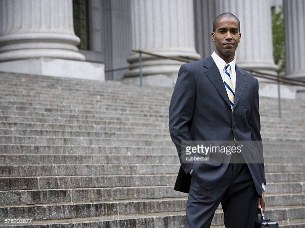 Portrait of a male lawyer standing on the steps of a courthouse and smiling
