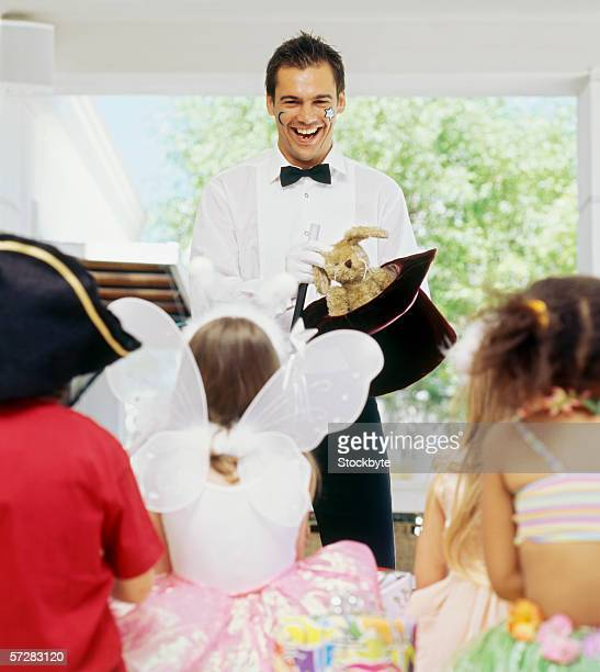 portrait of a male magician performing in front of a group of children at a birthday party - goochelaar stockfoto's en -beelden