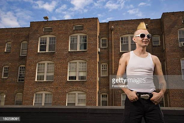 Portrait of a male punk standing in front of a building
