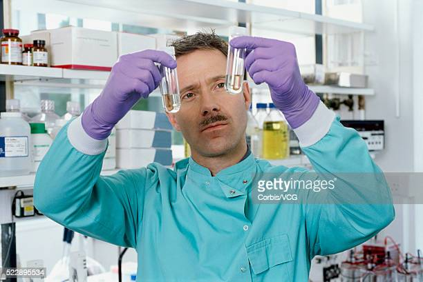 Portrait of a male scientist examining two test tubes in lab setting