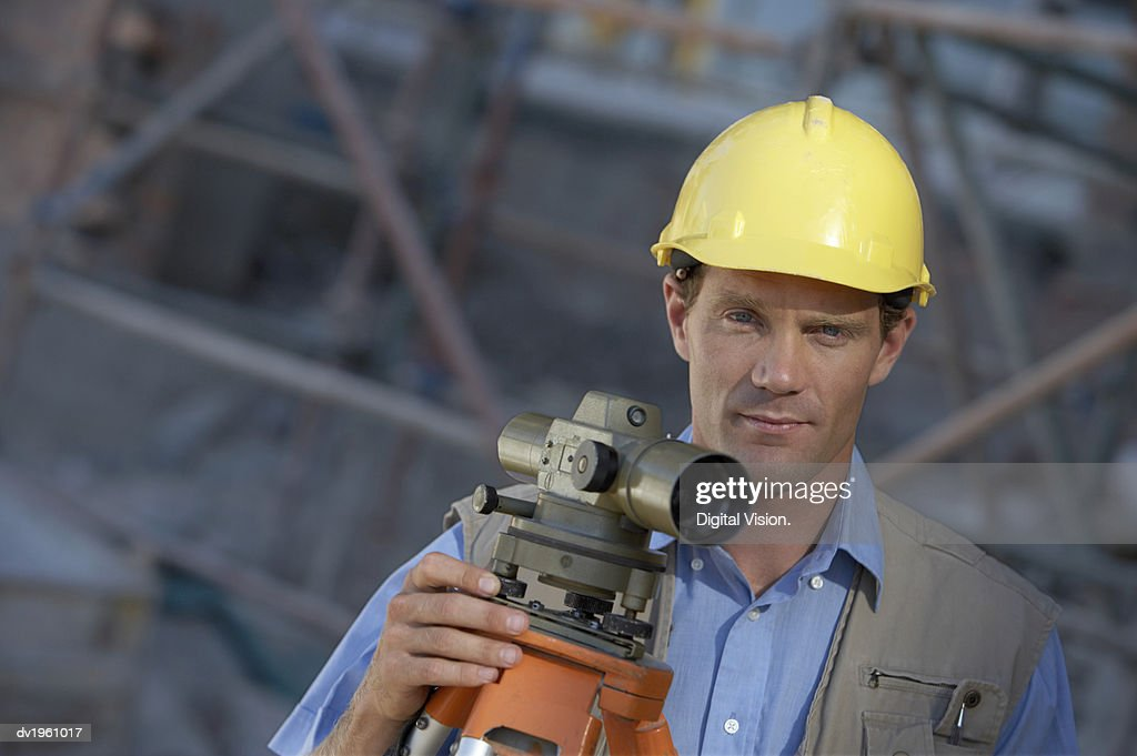 Portrait of a Male Surveyor Standing With a Theodolite : Stock Photo