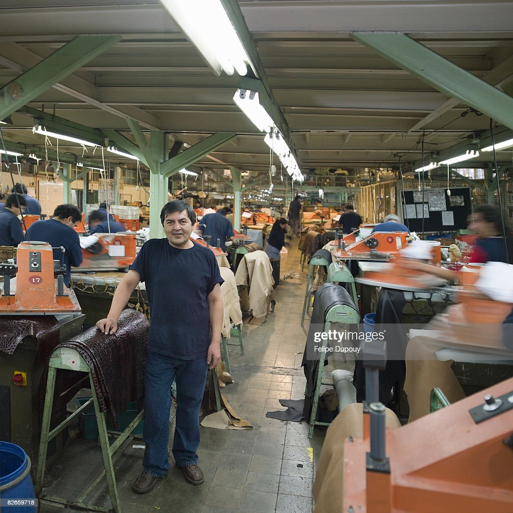 Portrait of a man amongst co-workers in a factory : Stock Photo