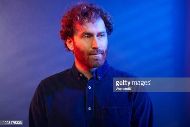 portrait of a man at a blue wall - farbbild stock-fotos und bilder