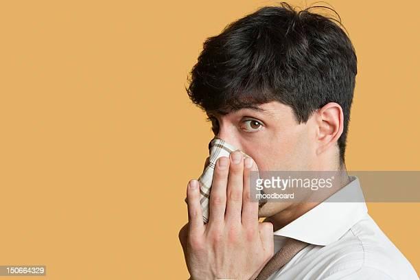 portrait of a man blowing his nose over colored background - sonarse fotografías e imágenes de stock