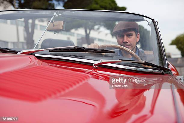 portrait of a man driving a red sports car - vintage car stock pictures, royalty-free photos & images