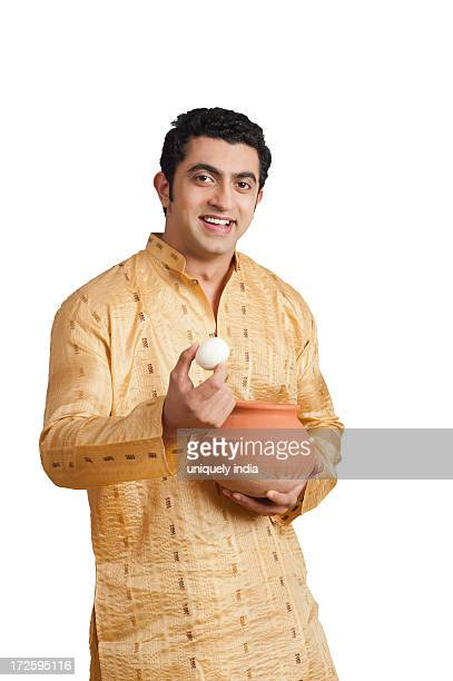 portrait of a man eating rasgulla and smiling - kurta stock pictures, royalty-free photos & images