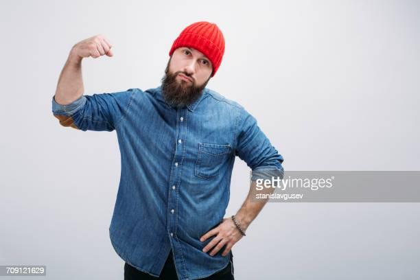 portrait of a man flexing his muscles - spieren spannen stockfoto's en -beelden