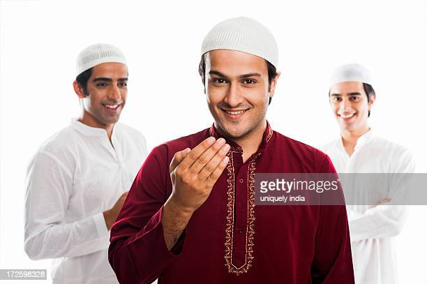 portrait of a man greeting and smiling with his friends in the background during eid festival - eid al adha stock pictures, royalty-free photos & images