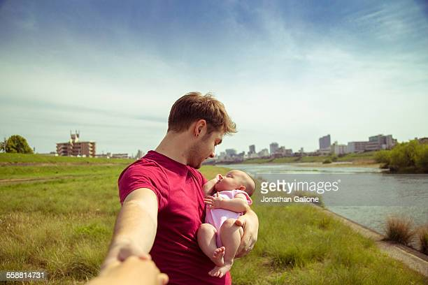 portrait of a man holding a baby girl - leanintogether stock pictures, royalty-free photos & images