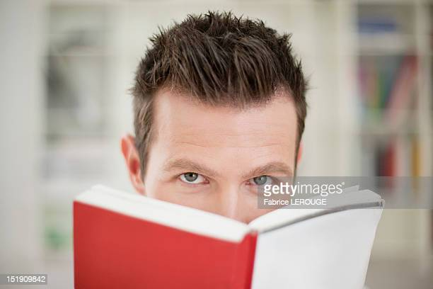 Portrait of a man holding a book in front of his face